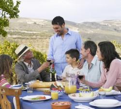Улыбающаяся семья на природе ест продукты Borges